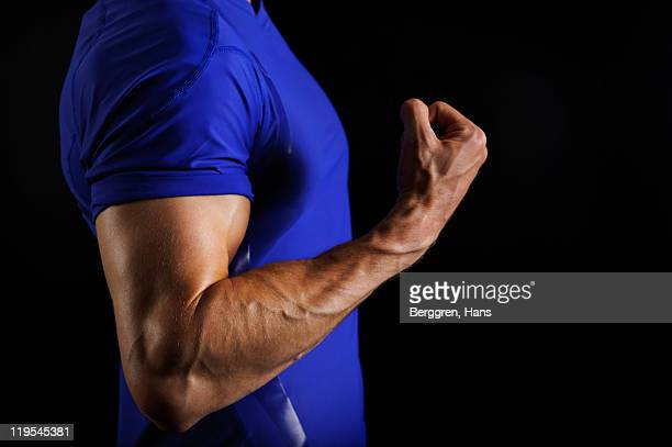 Male athlete flexing arm muscles