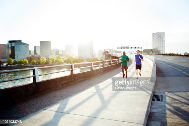 male athlete friends running on bridge against sky in city during sunny day - pedestrian walkway stock pictures, royalty-free photos & images
