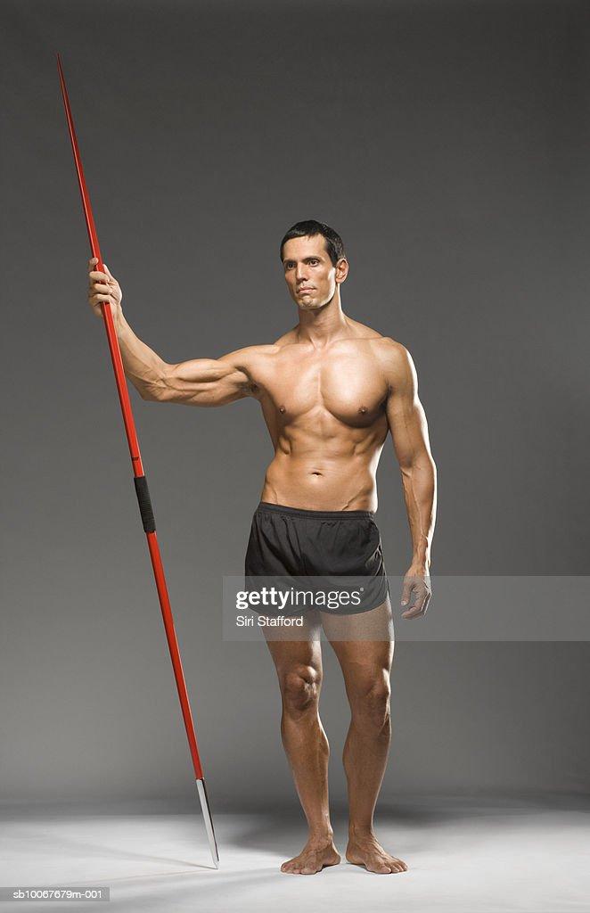 Male athlete holding javelin, studio shot : Stock Photo