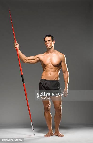Atleta masculino retención de jabalina; Foto de estudio