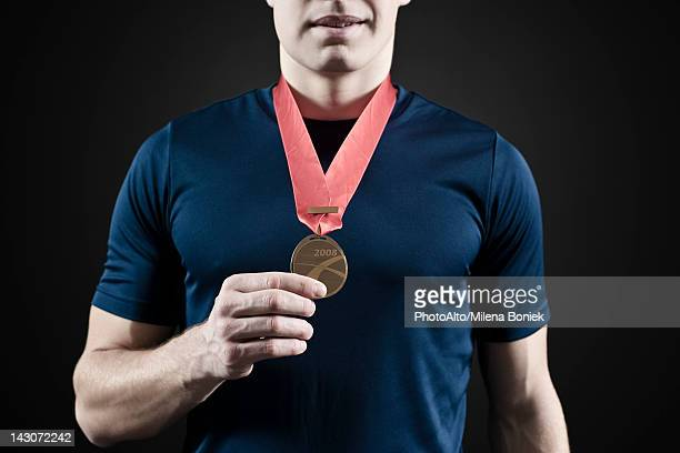 Male athlete holding medal, mid section
