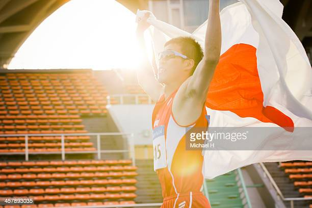 male athlete holding up Japanese flag