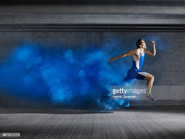 Male athlete leaping through smoke