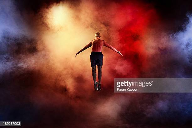 male athlete leaping with arms streched - dry ice stock pictures, royalty-free photos & images