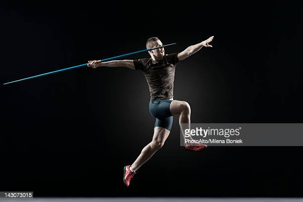male athlete leaping with javelin - やり投げ ストックフォトと画像