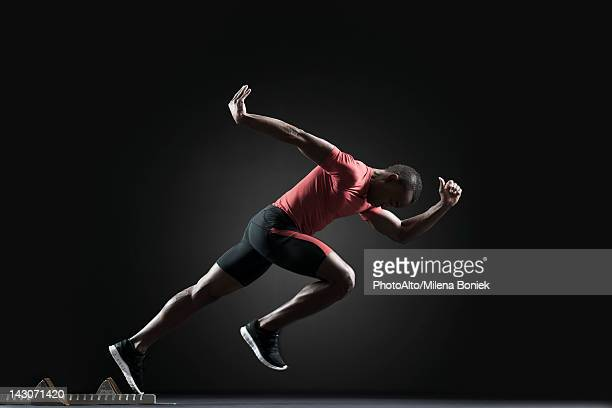 male athlete leaving starting block - athletics stock photos and pictures