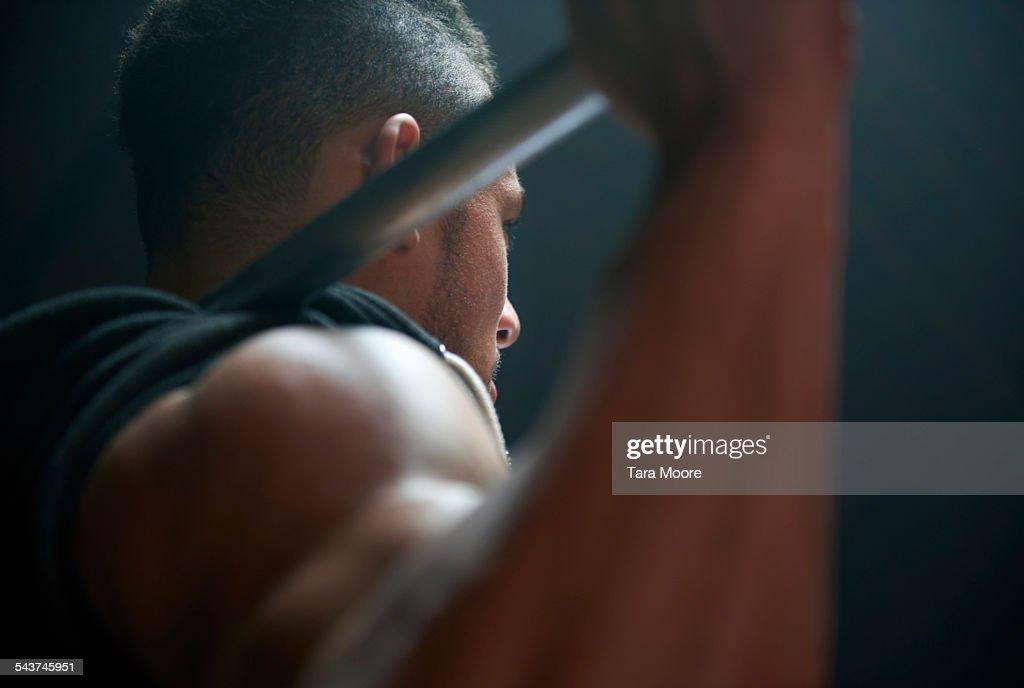 Male athlete lifting weight bar black background : Stock Photo