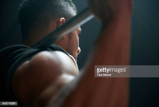Male athlete lifting weight bar black background