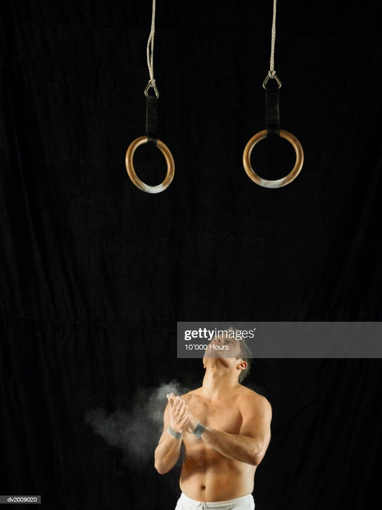 Male Athlete Looking up at Rings and Clapping His Hands With Chalk : Stock Photo