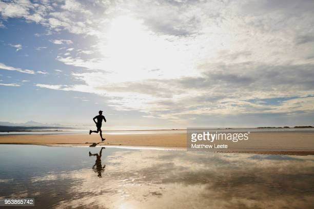 male athlete on beach at sunrise - matthew hale stock pictures, royalty-free photos & images