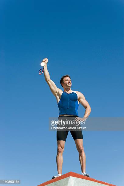 male athlete on podium, holding up gold medal - medalist stock photos and pictures