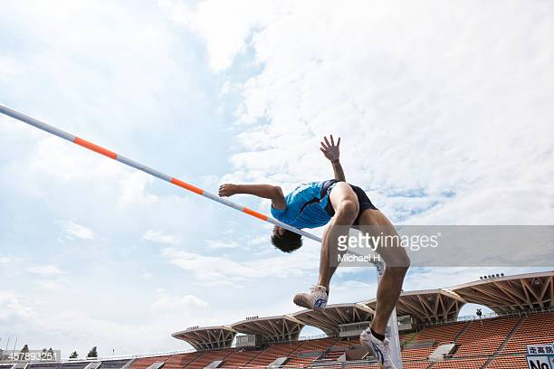 male athlete performing high jump - high jump stock pictures, royalty-free photos & images