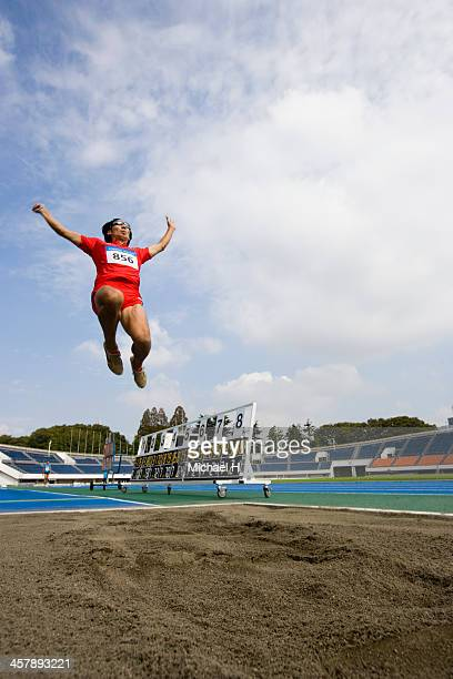 Male athlete performing long jump