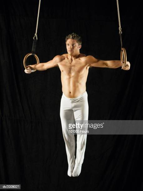 Male Athlete Practising a Rings Exercise