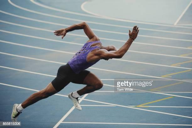 male athlete pushing out of the starting blocks as he starts his sprint race - esporte - fotografias e filmes do acervo