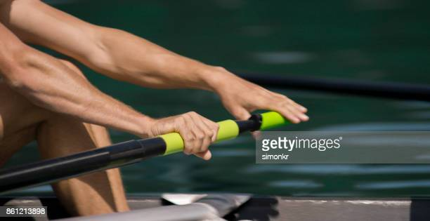 Male athlete rowing across lake in late afternoon