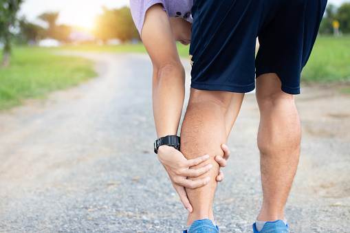 Male athlete runner muscle and ankle injury after jogging. Athlete man runner touching muscle in painful. Muscle and ankle injury concept. 1051391150
