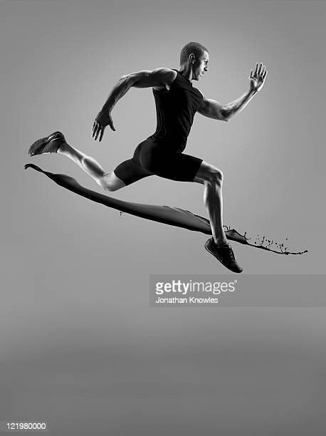 male athlete running above liquid splash - forward athlete stock pictures, royalty-free photos & images