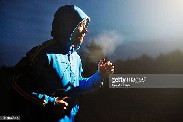 Male athlete running at night with mp3 player.