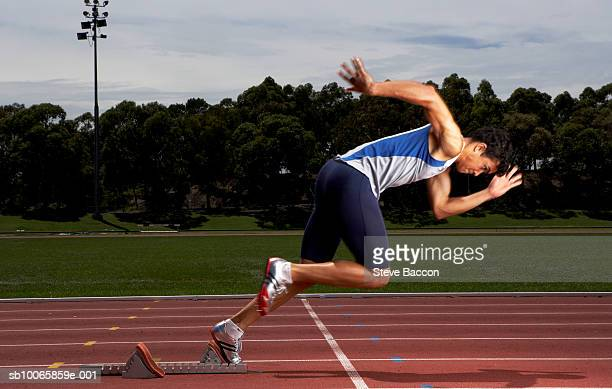 Male athlete running from starting block on track