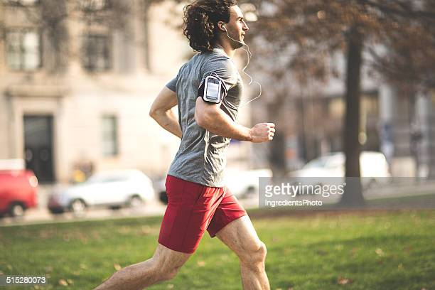 Male athlete running in the city park on early morning.