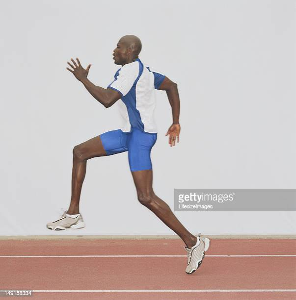 male athlete running on track, side view - men's track stock pictures, royalty-free photos & images