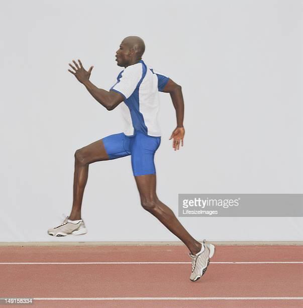 Atleta maschile in esecuzione su pista, vista laterale