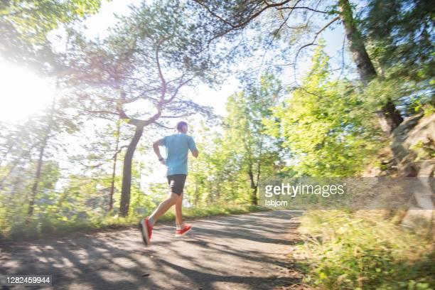 mannelijke atleet die in openlucht loopt. - uithoudingsvermogen stockfoto's en -beelden