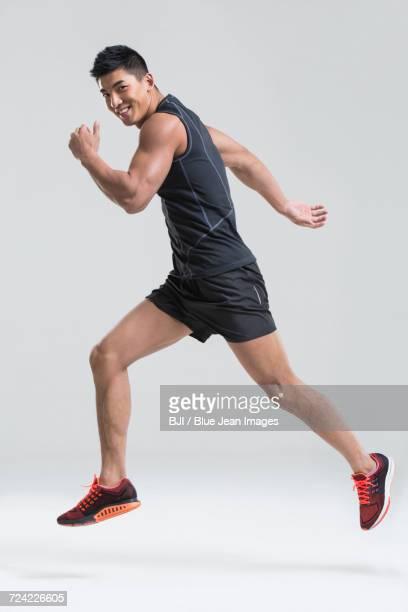 male athlete running - ランニングショートパンツ ストックフォトと画像