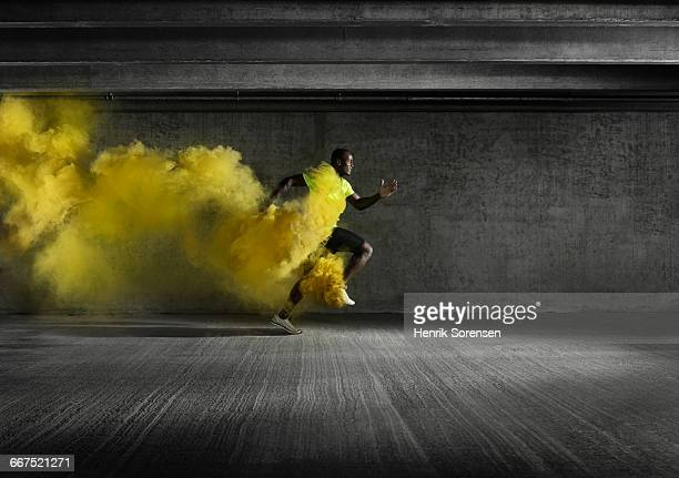 Male athlete running through smoke