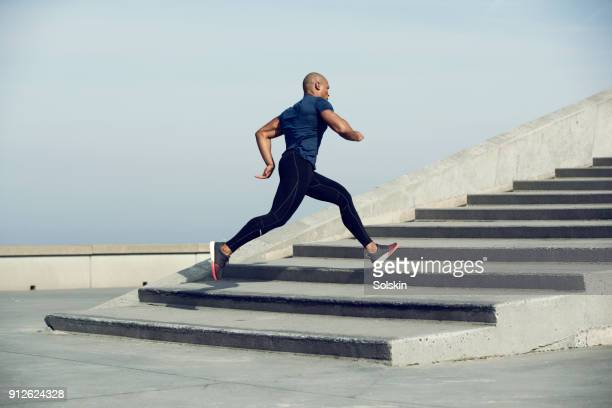 male athlete running up steps outdoors - 18 19 jahre stock-fotos und bilder