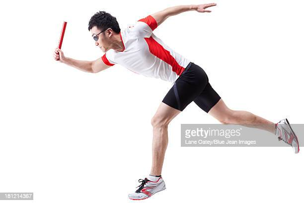 Male athlete running with relay baton
