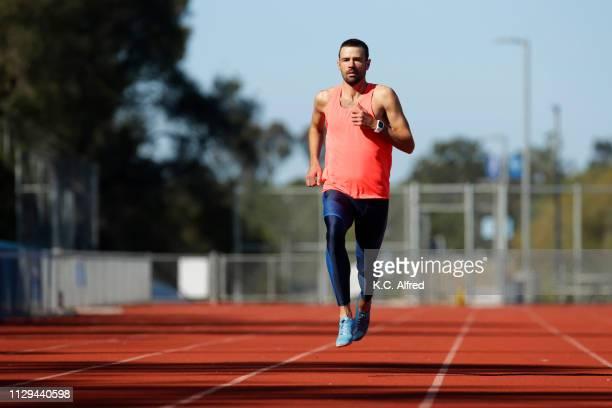 a male athlete runs on a track - baanevenement mannen stockfoto's en -beelden
