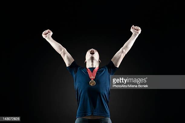 male athlete shouting with arms raised in victory - medalist stock pictures, royalty-free photos & images