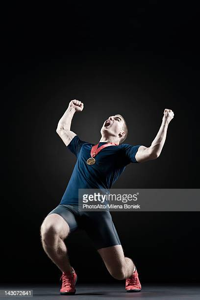 Male athlete shouting with arms raised in victory