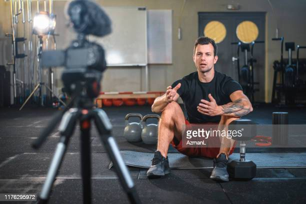 male athlete sitting on exercise mat and making vlog at gym - influencer stock pictures, royalty-free photos & images