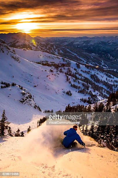 Male athlete skiing in deep powder during sunset.