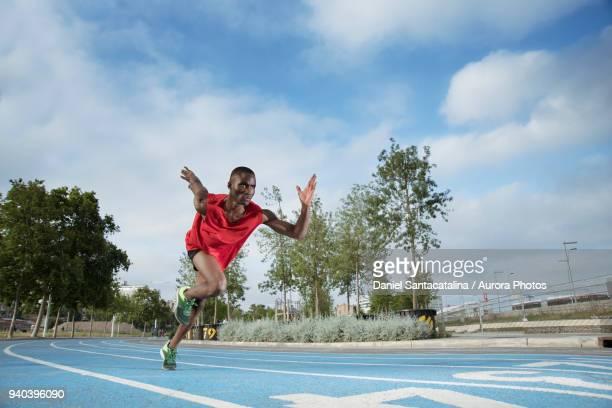 male athlete sprinting on all-weather running track, barcelona, spain - sprint - fotografias e filmes do acervo