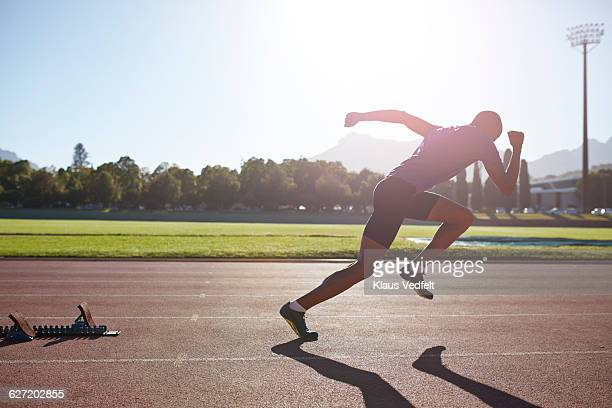 Male athlete sprinting out of start block