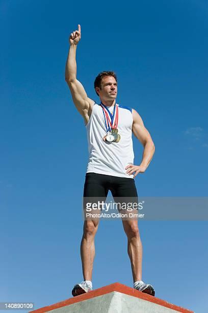 male athlete standing on winner's podium with hand raised in victory - winners podium stock-fotos und bilder