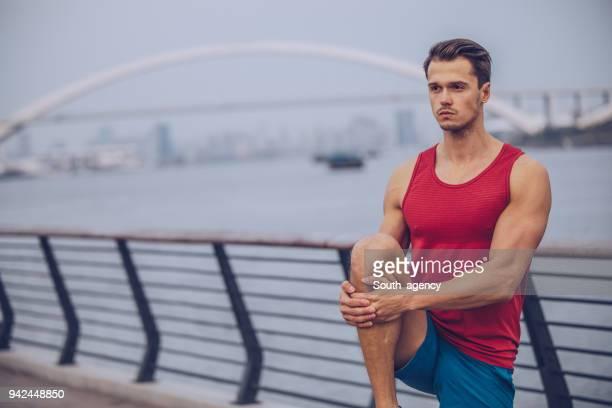atleta masculino estirando sus piernas - sin mangas fotografías e imágenes de stock