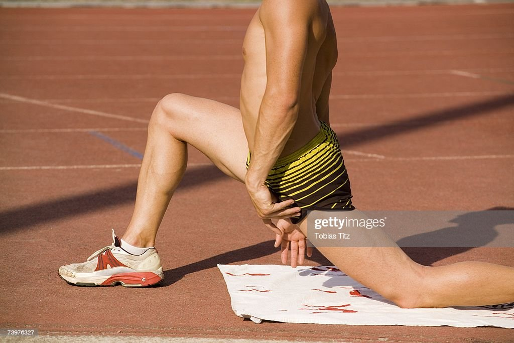 Male athlete stretching on the edge of a running track : Foto de stock