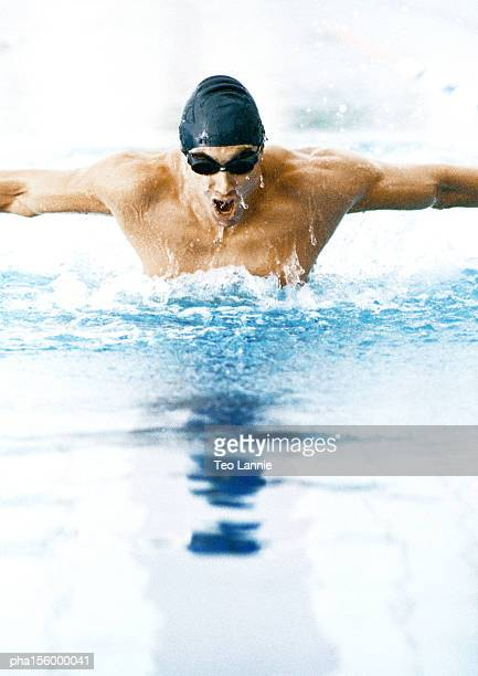 Male athlete swimming butterfly stroke, close-up