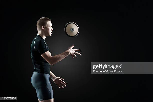 Male athlete throwing discus in air