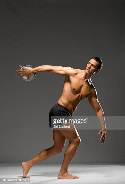 Männliche Athlet werfen Diskuswurf, Studioaufnahme