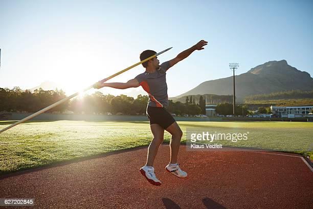 Male athlete throwing javelin at stadium