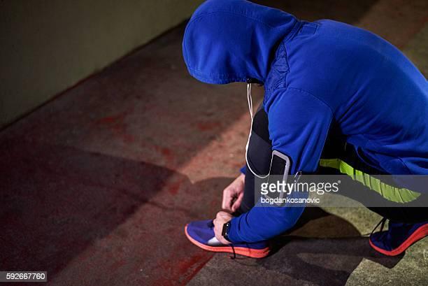 Male athlete tying shoelace during night cardio