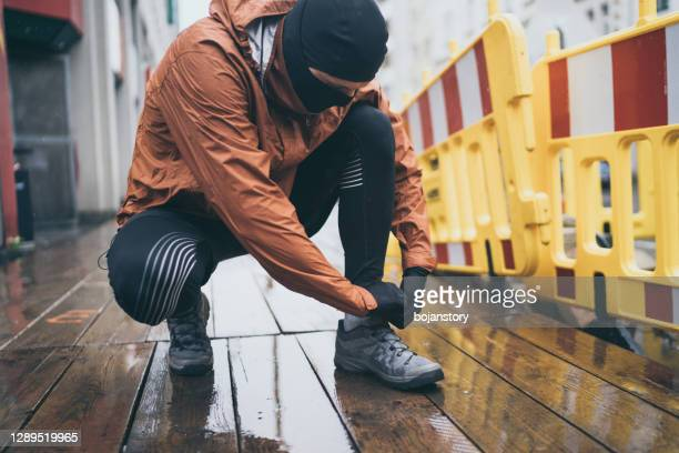 male athlete tying shoelace while jogging - lace glove stock pictures, royalty-free photos & images