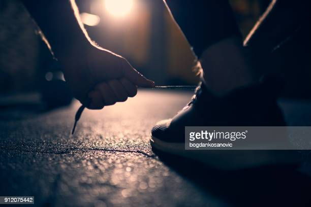 male athlete tying shoes - shoelace stock pictures, royalty-free photos & images