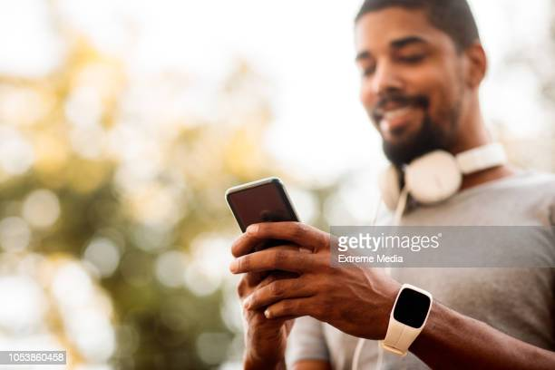 male athlete using mobile phone - mobile app stock pictures, royalty-free photos & images